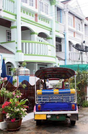 motorizado: Un taxi del tuk tukThai (rickshaw motorizado) parque� fuera de un hogar.