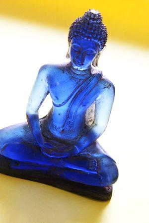 Blue Glas Buddha-Statue auf einem gelben Hintergrund Lizenzfreie Bilder