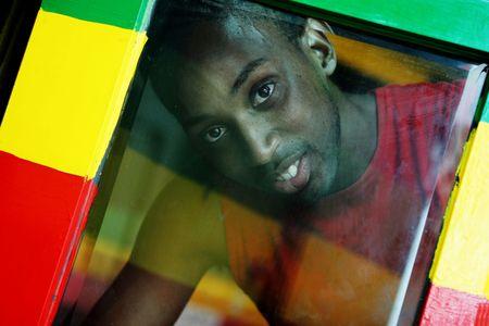 jamaican adult: Jamacian man looks through the window of a Reggae bar