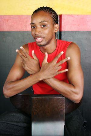 jamaican adult: Jamaican man sitting on a chair at a Reggae bar Stock Photo