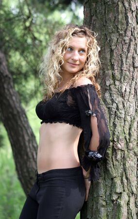 Beautiful blond woman leaning on a tree photo