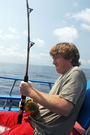 Man deep sea fishing. Pulling on the rod to catch a fish. photo