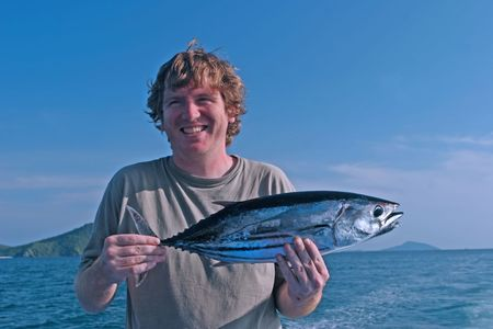 Man holds a fish caught during a deep sea fishing trip photo