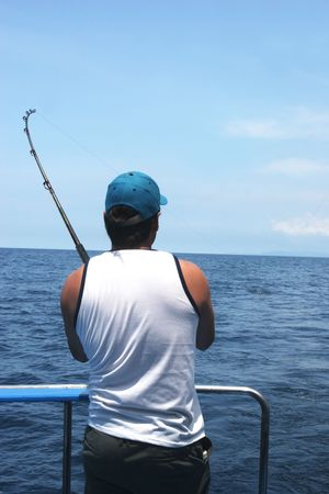 marina life: Man casting fishing rod into the ocean