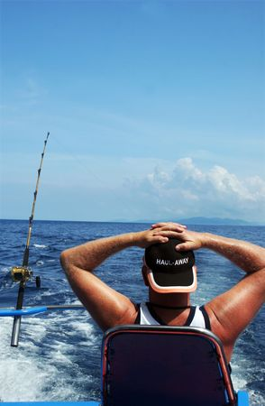 ocean fishing: Man deep sea fishing - man relaxing and waiting for the fish to bite
