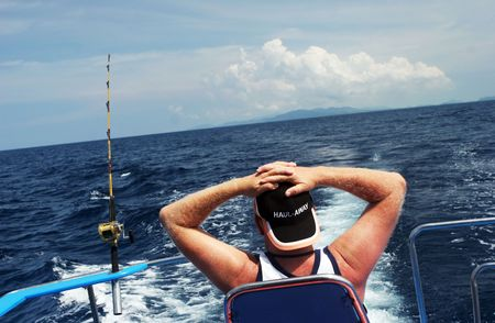 Man on a boat deep sea fishing is relaxing and waiting for the fish to come. photo