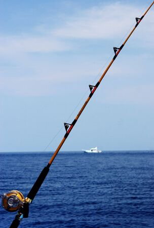 Fishing rod with boat in the background photo