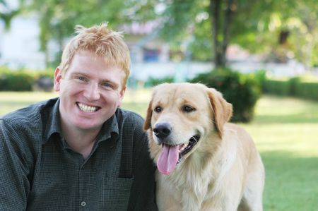 Happy blond man in the park with his dog