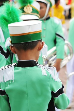 Young band member in a green uniform before a performance photo