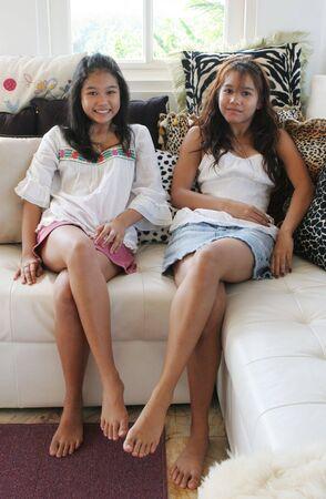 compa�erismo: Feliz hermanas de relax en el sof� en casa