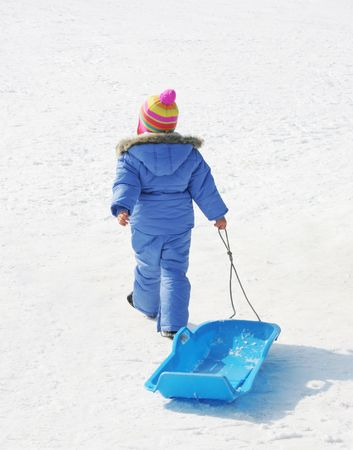 Little boy in colorful ski clothing dragging a sled in the snow Stock Photo - 715953