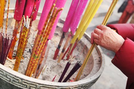 Close-up of an old womans hands as she offers incense at a temple in China - travel and tourism. photo