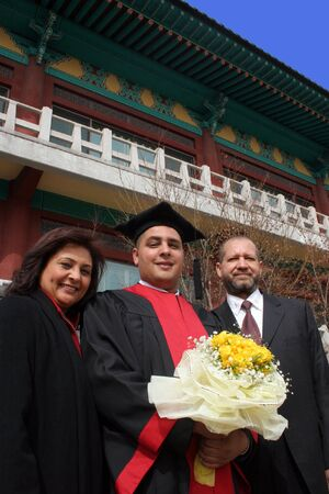 academic dress: Happy graduate with his mother and father.