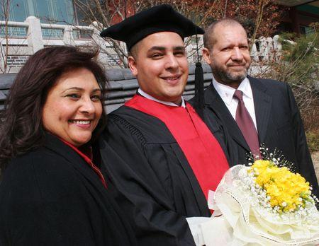 graduacion de universidad: Feliz se grad�an con su madre y padre.  Foto de archivo