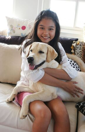 Happy Asian girl on animal print sofa with her pet dog