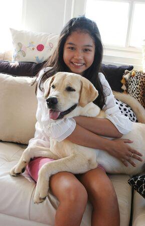 Happy Asiatin �ber tierische drucken Sofa mit ihrem Haustier Hund