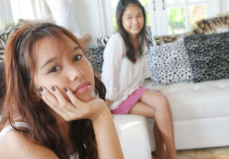 Unhappy Asian teenager with her sister in the background photo