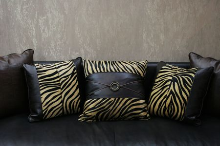 Modern couch with leather leopard skin cushions (copy space) - home interiors Stock Photo