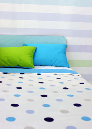 Bed with bright blue and green linen - home inters Stock Photo - 827903