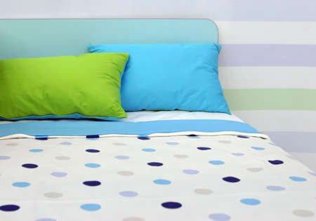 Bed with bright blue and green linen - home interiors Stock Photo