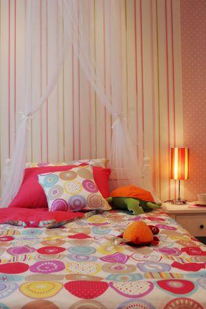 Schlafzimmer des h�bschen rosafarbenen Kindes mit Spielwaren auf dem Bett - Hauptinneren