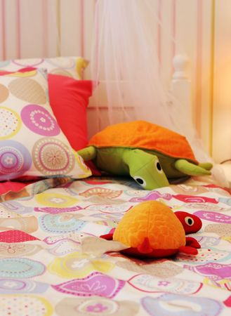 Pretty pink childs bedroom with stuffed turtles on the bed - home interiors Stock Photo