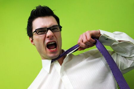 appealing attractive: Frustrated businessman pulls at his tie and screams.