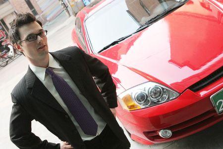 Gesch�ftsmann in einer Klage vor einem roten Auto