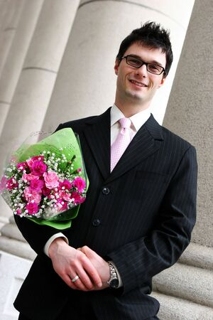 Attractive young man has pink bouquet of flowers for his girlfriend.