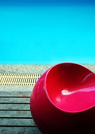 Bright red retro chair next to a swimming pool
