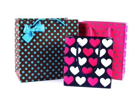 Three bright gift bags isolated on white photo