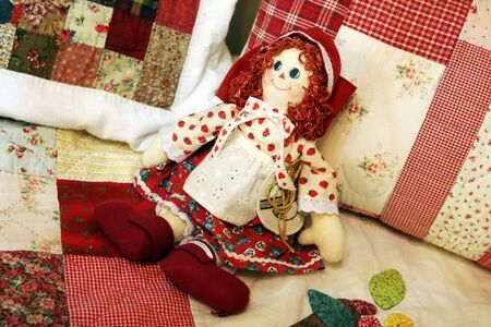 collectable: Pretty patchwork quilt doll on a bed