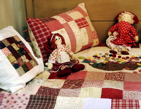 collectable: Pretty patchwork quilt dolls on a bed