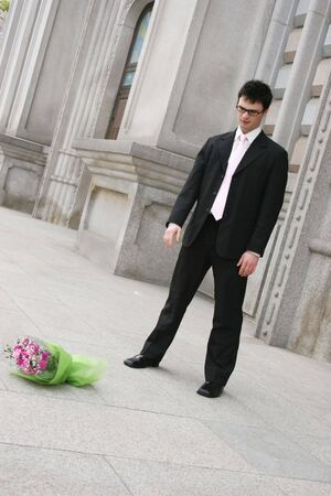 stood up: Man throws a bouquet of flowers to the ground after being stood up for a date Stock Photo