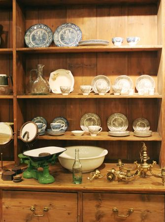 Wooden cabinet displaying antique objects including plates and tea cups.