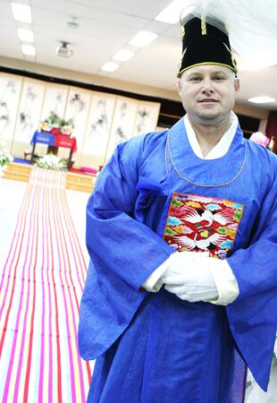 Western man prepares to marry his South Korean bride in a traditional ceremony - travel and tourism. Stock Photo