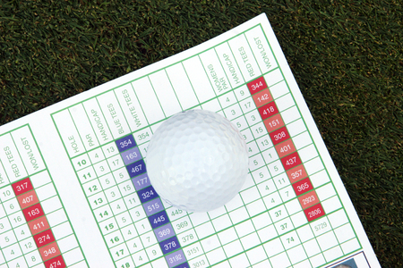 Golf score card and golf ball on grass. Stock Photo
