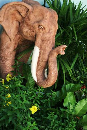 Wooden elephant statue in a garden. photo