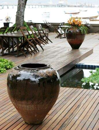 seating area: Ceramic pot at an outdoor seating area of a restaurant by the beach - travel and tourism.