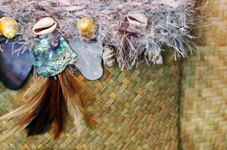 new zealand flax: Close-up of traditional New Zealand Maori design - paua, shells, feather and flax. Stock Photo
