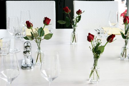Elegant table setting with vases of red roses and white linen. Stock Photo - 2229314
