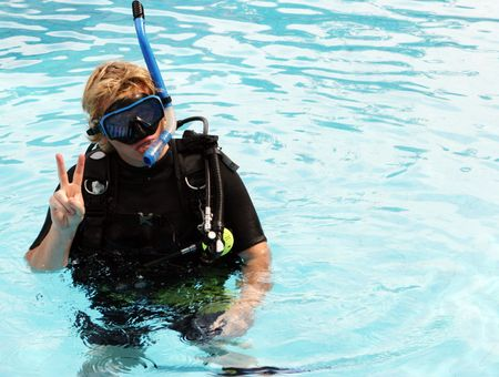 skindiver: Scuba diver in the swimming pool giving a signal.