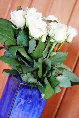homeware: White roses in a blue ceramic vase.