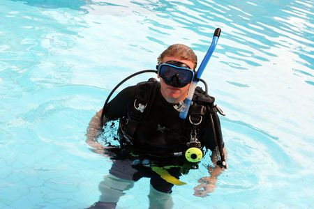 skindiver: Man in scuba gear in a swimming pool.