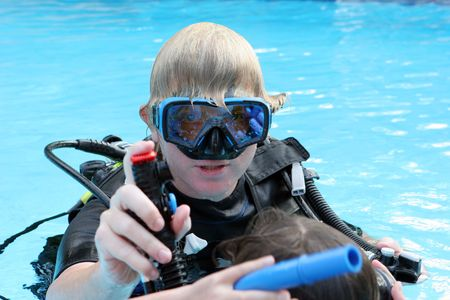 Scuba diving instructor demonstates a skill to a student in a swimming pool. photo