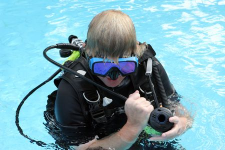 skindiver: Scuba diving instructor demonstates a skill in a swimming pool.