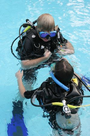scuba goggles: Scuba diving instructor demonstates a skill to a student in a swimming pool.