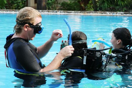 wetsuit: Scuba diving instructor demonstates a skill to a student in a swimming pool.