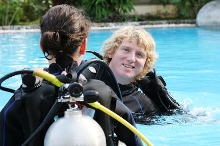 skindiver: Scuba diving instructor demonstates a skill to a student in a swimming pool.