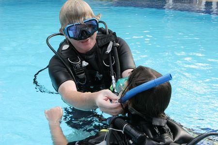 Scuba diving instructor demonstates a skill to a student in a swimming pool.